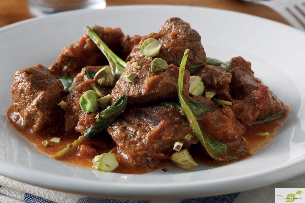 In kruiden gestoofd lamsvlees met bladspinazie en pistachenoten
