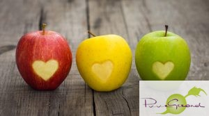 Three apples with  engraved hearts on wood background